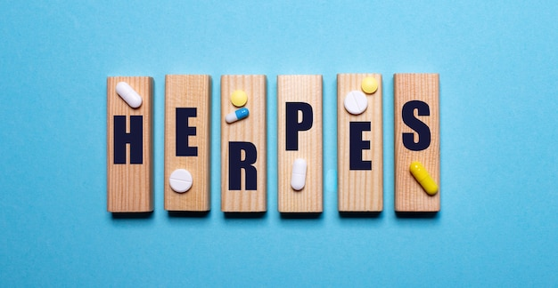 파란색 배경에 단어 herpes 및 알약과 나무 블록. 의료 개념