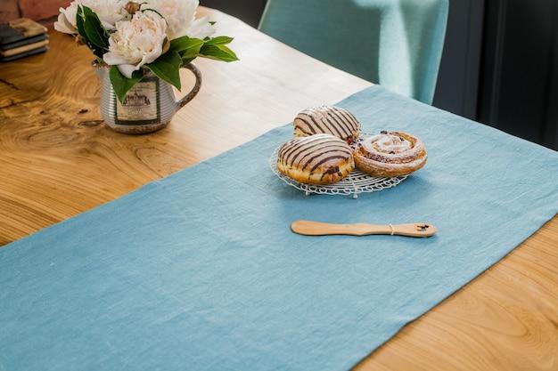 На синей льняной салфетке на деревянном столе лежит букет нежных розовых пионов и лежат сладкие булочки.
