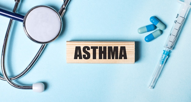 На синей поверхности стетоскоп, шприц, таблетки и деревянный брусок с надписью asthma. медицинская концепция