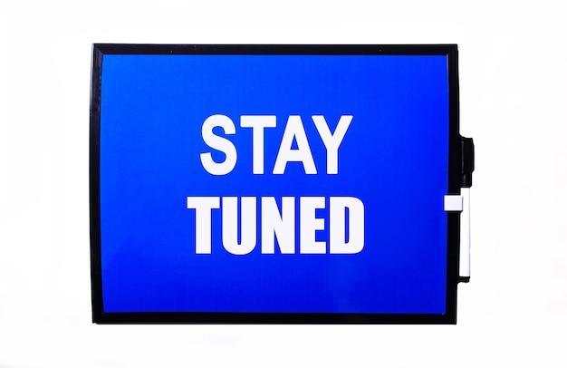 На синей поверхности белая надпись stay tuned.