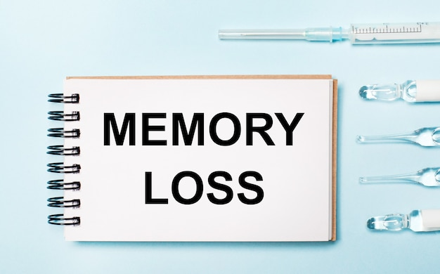 의약품이 들어있는 파란색 표면 앰플과 loss of memory라는 텍스트가있는 노트북. 의료 개념