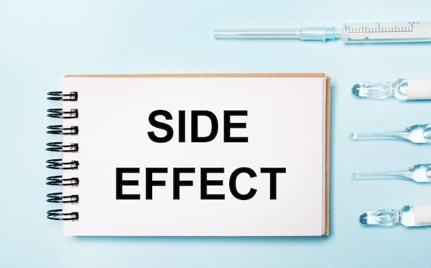 薬が入った青い表面のアンプルと「副作用」というテキストが書かれたノート