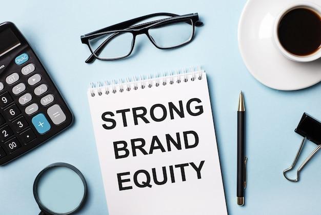 На синей поверхности очки, калькулятор, кофе, лупа, ручка и блокнот с текстом strong brand equity.