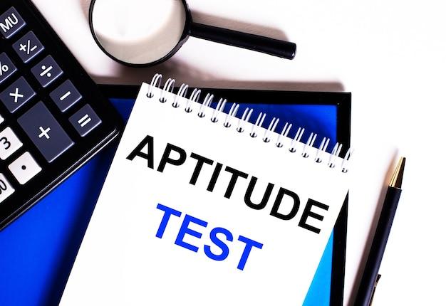 На синей поверхности возле калькулятора, лупы и ручки блокнот с надписью aptitude test.