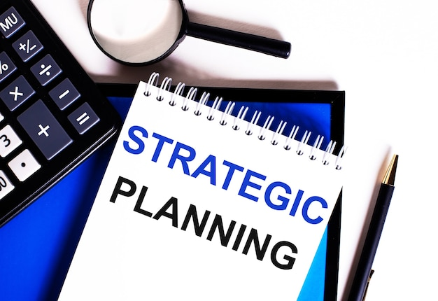 На синей поверхности возле калькулятора, лупы и ручки блокнот с надписью стратегическое планирование.