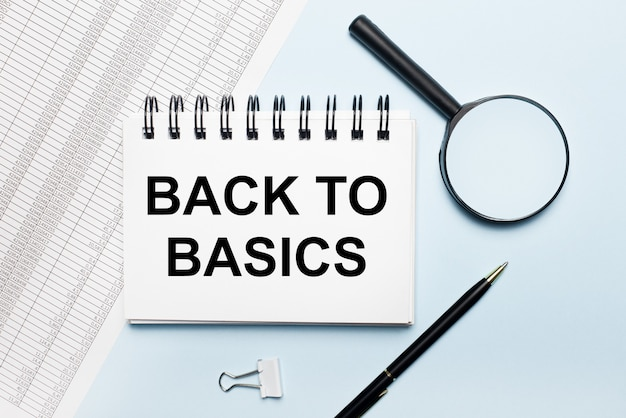 青い表面に、レポート、虫眼鏡、ペン、および「基本に戻る」というテキストが記載されたノートブック。ビジネスコンセプト。フラットレイ