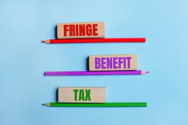 파란색 표면에 색연필 3 개, fringe benefit tax라는 텍스트가있는 나무 블록 3 개