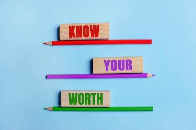 파란색 표면에 세 개의 색연필, 텍스트가있는 나무 블록 세 개 know your worth