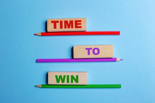 파란색 표면에 색연필 3 개, time to win 텍스트가있는 나무 블록 3 개