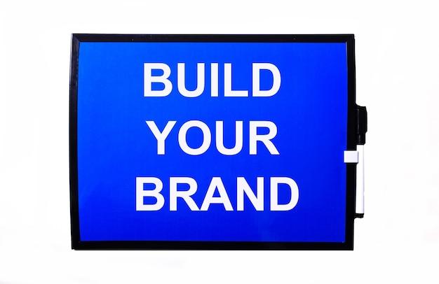 На синей стене белая надпись build your brand