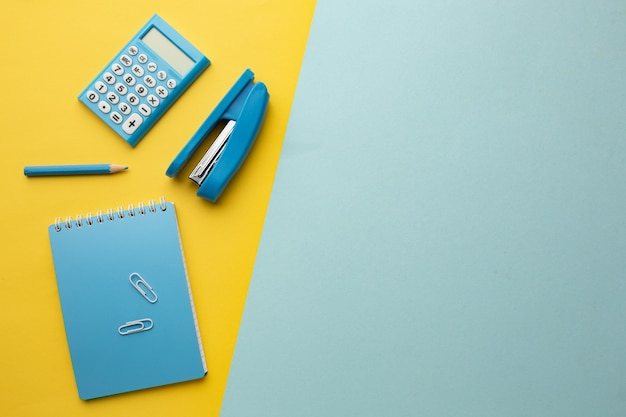 파란색 노란색 배경에는 계산기, 노트북, 스테이플러, 연필이 있습니다. 비문을위한 공간.