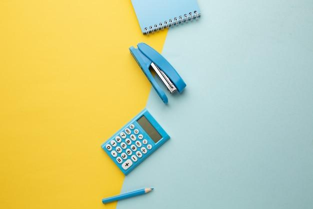 На сине-желтом фоне калькулятор, блокнот, степлер, карандаш.