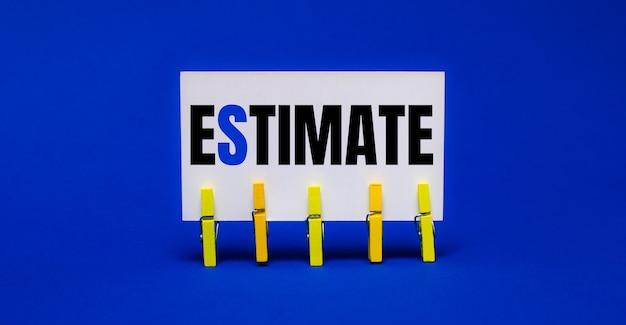 黄色の洗濯バサミの明るい青色の背景に、estimateというテキストが付いた白いカード