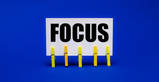 На ярко-синем фоне на желтых прищепках белая карточка с текстом focus.