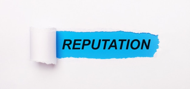 На ярко-синем фоне белая бумага с рваной полосой и надписью репутация.