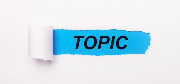 На ярко-синем фоне белая бумага с рваной полосой и текстом тема.