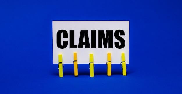 黄色の洗濯バサミの明るい青いテーブルに、claimsというテキストが書かれた白いカード