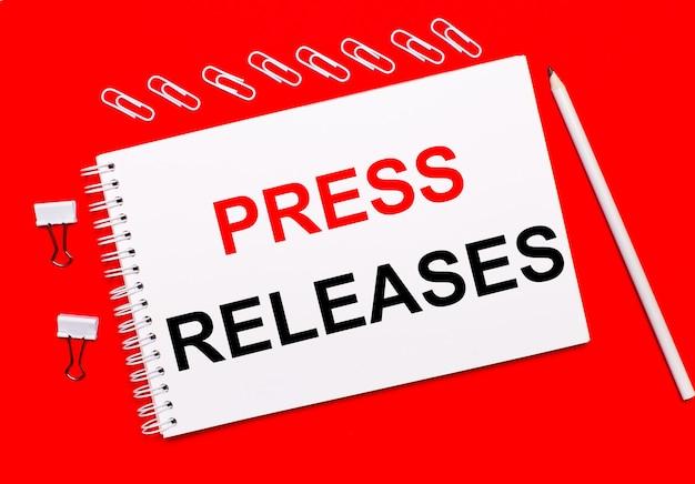 밝은 빨간색 배경에 흰색 연필, 흰색 종이 클립 및 press releases라는 텍스트가 있는 흰색 공책