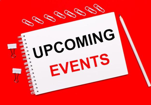 真っ赤な背景に、白い鉛筆、白いペーパークリップ、白いノートに「今後のイベント」というテキストが表示されます。