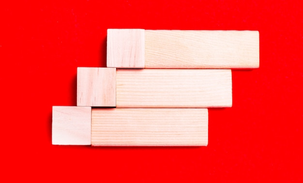 На ярко-красном фоне светлые деревянные блоки и кубики с местом для вставки текста.