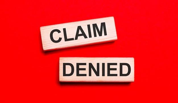 밝은 빨간색 배경에 claim denied라는 텍스트가 있는 두 개의 밝은 나무 블록이 있습니다.