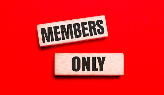 真っ赤な背景に、「メンバーのみ」というテキストが付いた2つの明るい木製のブロックがあります。