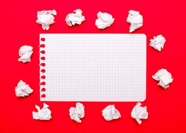 На ярко-красном фоне белые скомканные бумажки и лист бумаги с местом для вставки текста. шаблон