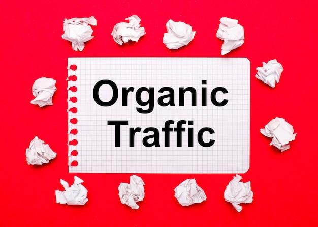 На ярко-красном фоне белые мятые листы бумаги и лист с текстом organic traffic.