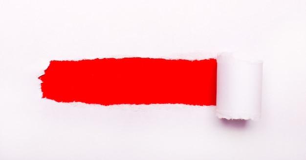 真っ赤な背景に、破れたストリップとテキストを挿入する場所のある白い紙。レンプレート
