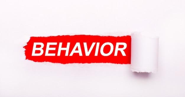 На ярко-красном фоне белая бумага с рваной полосой и надписью behavior.