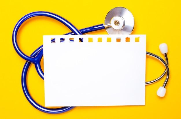 На ярко-желтом фоне синий стетоскоп и лист бумаги с местом для вставки текста. медицинская концепция