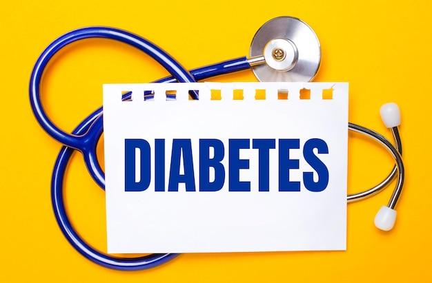 На ярко-желтом фоне синий стетоскоп и лист бумаги с надписью «диабет». медицинская концепция