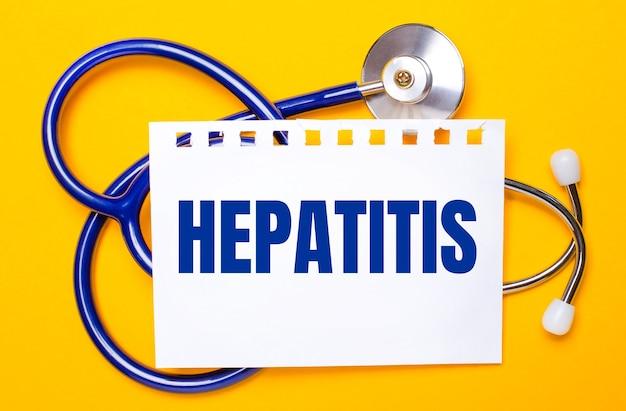 明るい黄色の背景に、青い聴診器とhepatitisというテキストが書かれた1枚の紙。医療コンセプト