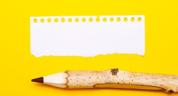 明るい黄色の背景に、大きな木製の鉛筆と、テキストを挿入する場所のある破れた紙のシート。