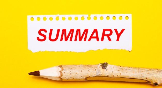 明るい黄色の背景に、大きな木製の鉛筆と、summaryというテキストが書かれた破れた紙のシート。