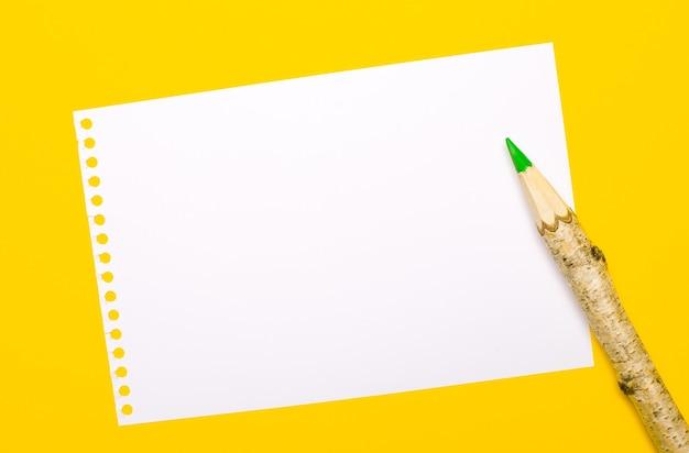 明るい黄色の背景に、大きな木製の鉛筆とテキストを挿入する場所のある白い紙。