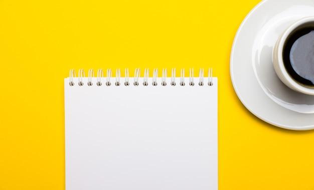 밝은 노란색 배경에 커피가 담긴 흰색 컵과 텍스트 또는 일러스트레이션을 삽입 할 수있는 빈 흰색 노트북이 있습니다. 복사 공간이있는 평면도