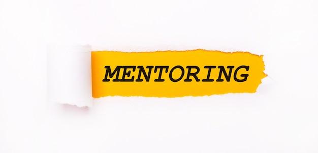 На ярко-желтом фоне белая бумага с рваной полосой и надписью mentoring.