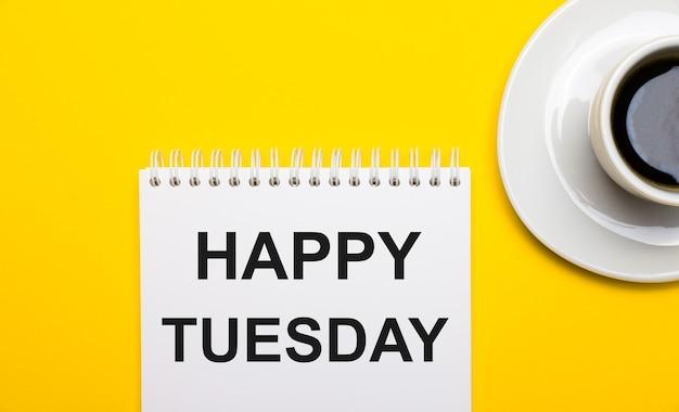На ярко-желтой поверхности белая чашка с кофе и белый блокнот с надписью happy tuesday.