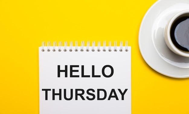 На ярко-желтой поверхности белая чашка с кофе и белый блокнот с надписью hello thursday.