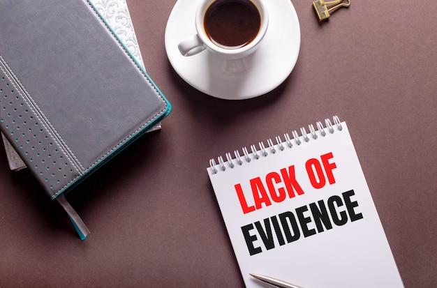 На коричневой поверхности дневники, белая чашка кофе и блокнот с отсутствием доказательств.