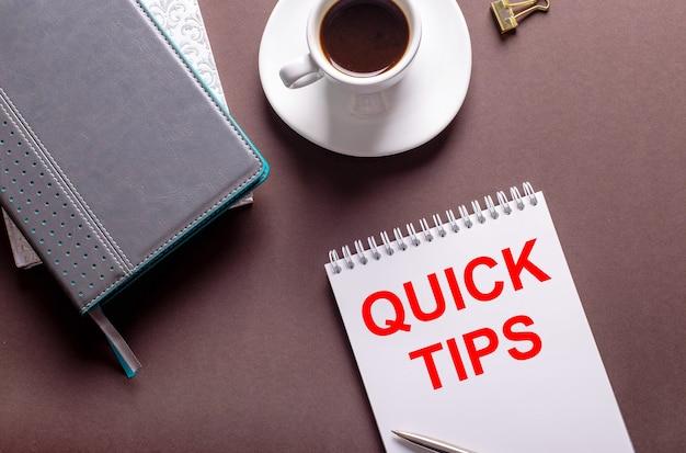 갈색 표면에 일기, 흰색 컵의 커피 및 빠른 팁이있는 노트북