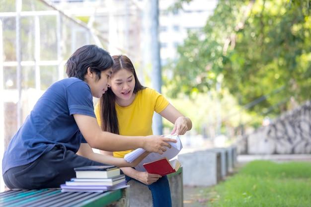 В кампусе пара студентов учится вместе, а подросток сидит на скамейке рядом со спортивной площадкой с книгой.