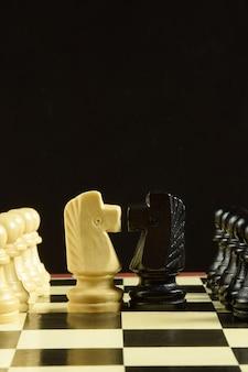 На шахматной доске противоположны белые и черные шахматные фигуры. впереди фигуры лошадей.