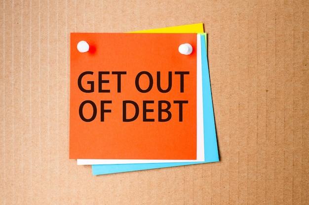 クラフト紙の表面に-getout ofdebtというテキストが付いた明るい赤の四角いステッカー