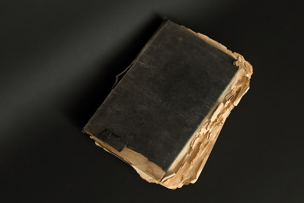 어두운 배경에는 낡은 페이지가있는 매우 오래된 책이 있습니다.