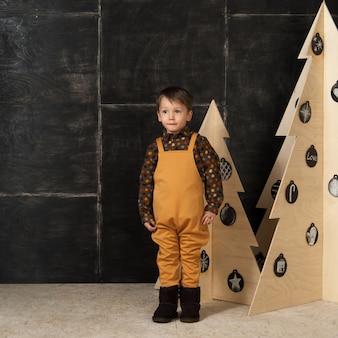 暗い背景に木で作られたクリスマスツリーの近くでファッショナブルな衣装でポーズをとる小さな男の子