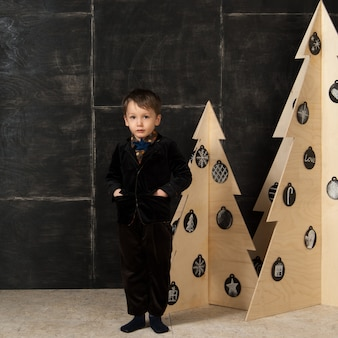 暗い背景に木で作られたクリスマスツリーの近くでスタイリッシュな衣装でポーズをとる小さな男の子