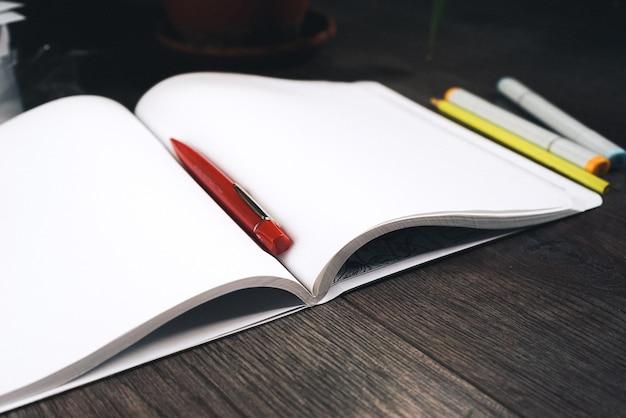어두운 나무 표면에 흰색 공책과 펜이 있습니다