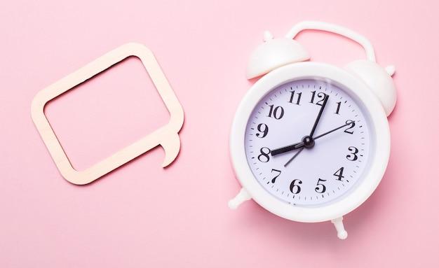 繊細なピンクの背景、白い目覚まし時計、テキストやイラストを挿入する場所のあるフレーム。レンプレート